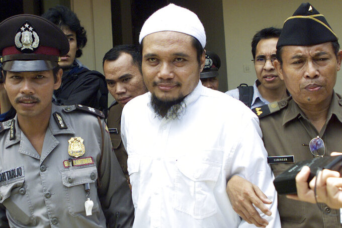 FILE - Militant cleric Abu Rusdan, center, is escorted by security officers after his trial hearing at a district court in Jakarta, Indonesia, in this Monday, Nov. 3, 2003 file photo. Indonesia's elite counterterrorism squad has arrested the convicted militant and suspected leader of an al-Qaida-linked group that has been blamed for a string of past bombings in the country, Indonesia police said Monday, Sept. 13, 2021. (AP Photo/Tatan Syuflana, File)