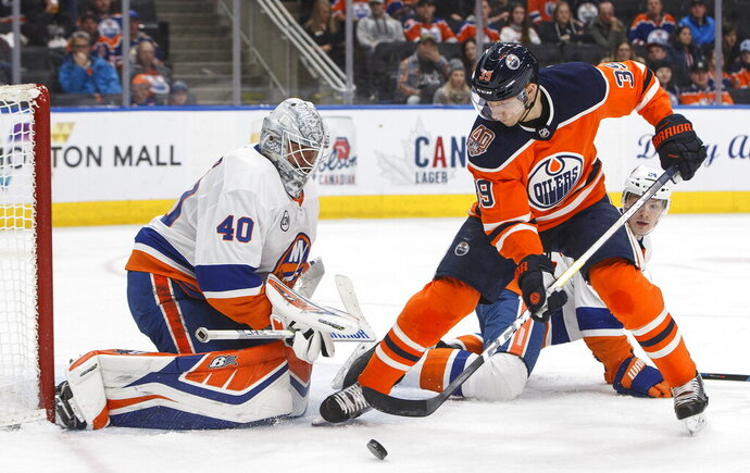 New York Islanders goalie Robin Lehner (40) makes a save against Edmonton Oilers' Alex Chiasson (39) as Islanders' Scott Mayfield (24) tries to defend during second-period NHL hockey game action in Edmonton, Alberta, Thursday, Feb. 21, 2019. (Jason Franson/The Canadian Press via AP)