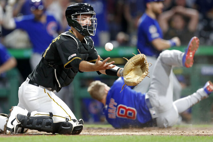 Chicago Cubs' Ian Happ (8) tumbles away after scoring from first on a triple by Tony Kemp as Pittsburgh Pirates catcher Jacob Stallings, left, tries to control the ball in the eighth inning of a baseball game, Friday, Aug. 16, 2019, in Pittsburgh. (AP Photo/Keith Srakocic)