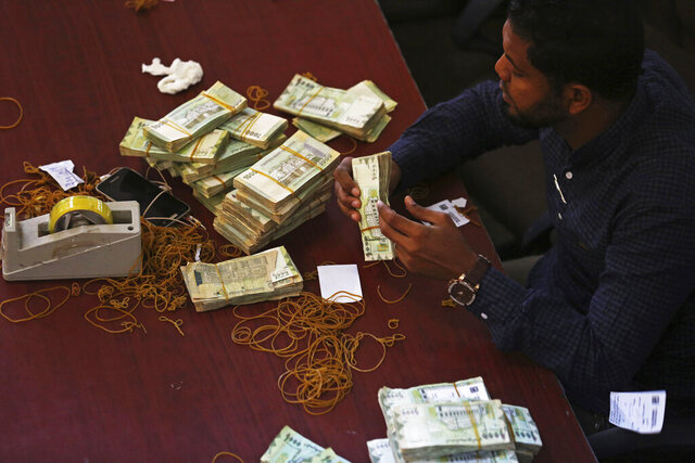 """FILE - In this Dec. 13, 2018 file photo, a worker counts money at the Central Bank of Yemen's internationally recognized government in Aden, Yemen. A report by a panel of U.N. experts released Tuesday, Jan. 26, 2021,  accused the government of implementing a scheme in 2019 to illegally divert to traders $423 million in Saudi money. The funds were meant to buy rice and other supplies for Yemenis who have been suffering from a protracted military conflict since 2014, the report said.The Central Bank of Yemen said Wednesday the report was based on """"misleading claims and information"""" propagated by """"enemies of Yemen.""""  (AP Photo/Jon Gambrell, File)"""