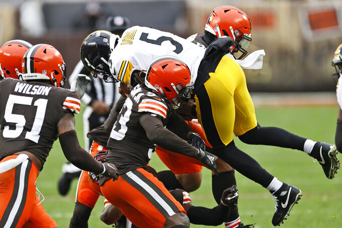 Pittsburgh Steelers quarterback Joshua Dobbs (5) is tackled after a rushing play during the first half of an NFL football game against the Cleveland Browns, Sunday, Jan. 3, 2021, in Cleveland. (AP Photo/Ron Schwane)