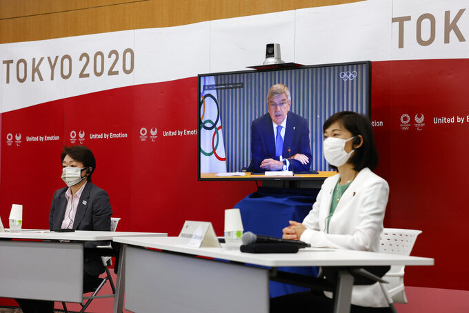 Tokyo 2020 President Seiko Hashimoto, left, Japanese Olympic Minister Tamayo Marukawa, right, and IOC President Thomas Bach, on a screen, attend a five-party online meeting at Harumi Island Triton Square Tower Y in Tokyo Monday, June 21, 2021. The Tokyo Olympics will allow some local fans to attend when the games open in just over a month, Tokyo organizing committee officials and the IOC said on Monday. (Rodrigo Reyes Marin/Pool Photo via AP)