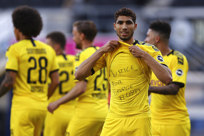 Achraf Hakimi Mouh of Borussia Dortmund celebrates scoring his teams fourth goal of the game with a 'Justice for George Floyd' shirt during the German Bundesliga soccer match between SC Paderborn 07 and Borussia Dortmund at Benteler Arena in Paderborn, Germany, Sunday, May 31, 2020. Because of the coronavirus outbreak all soccer matches of the German Bundesliga take place without spectators. (Lars Baron/Pool via AP)