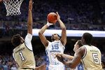North Carolina forward Garrison Brooks (15) shoots while Georgia Tech forwards James Banks III (1) and Moses Wright (5) defend during the first half of an NCAA college basketball game in Chapel Hill, N.C., Saturday, Jan. 4, 2020. (AP Photo/Gerry Broome)