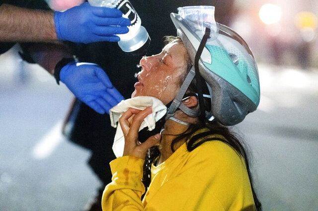 A medic treats Black Lives Matter protester Lacey Wambalaba after exposure to chemical irritants deployed by federal officers at the Mark O. Hatfield United States Courthouse on Friday, July 24, 2020, in Portland, Ore. Since federal officers arrived in downtown Portland in early July, violent protests have largely been limited to a two block radius from the courthouse. (AP Photo/Noah Berger)