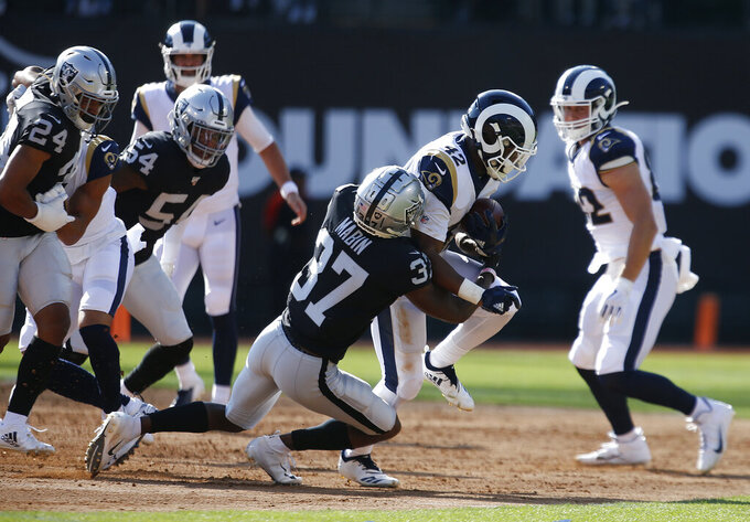 Oakland Raiders' Dylan Mabin (37) tackles Los Angeles Rams' John Kelly (42) during the first half of a preseason NFL football game Saturday, Aug. 10, 2019, in Oakland, Calif. (AP Photo/Rich Pedroncelli)