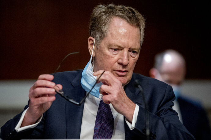 U.S. Trade Representative Robert Lighthizer takes off his mask as he arrives at a Senate Finance Committee hearing on U.S. trade on Capitol Hill, Wednesday, June 17, 2020, in Washington. (AP Photo/Andrew Harnik, Pool)
