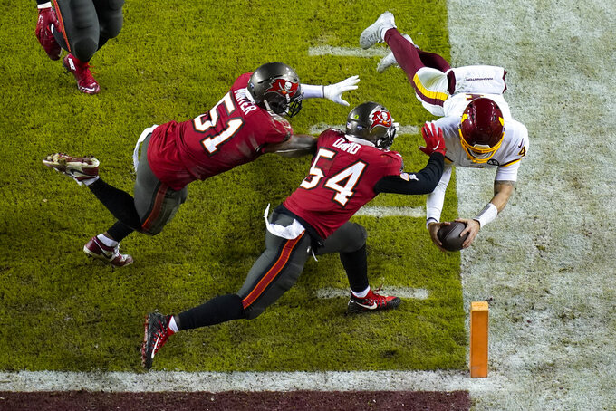 Washington Football Team quarterback Taylor Heinicke (4) dives toward the end zone to score a touchdown against Tampa Bay Buccaneers inside linebackers Kevin Minter (51) and Lavonte David (54) during the second half of an NFL wild-card playoff football game, Saturday, Jan. 9, 2021, in Landover, Md. (AP Photo/Al Drago)