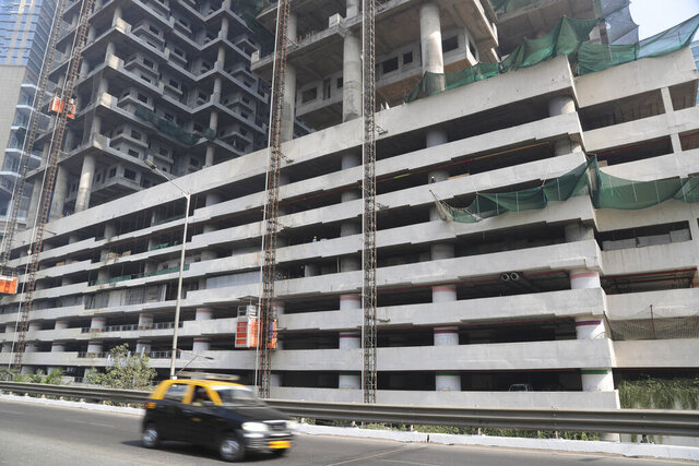 File- In this Tuesday, Jan. 21, 2020, file photo, a car drives past an under-construction building in Mumbai, India, Tuesday, Jan. 21, 2020. India's government expects the economy to expand up to 6.5% in the next fiscal year, starting in April, and hopes to follow China's example in developing labor intensive industries and exports. (AP Photo/Rafiq Maqbool, File)