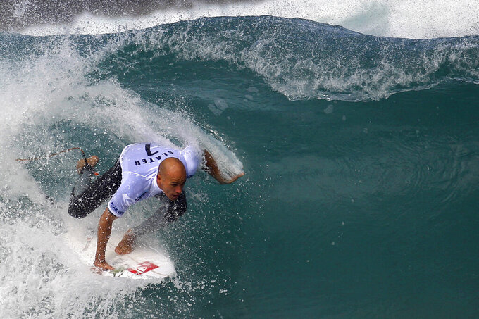 FILE - In this Tuesday May 17, 2011, file photo, Kelly Slater of the U.S. competes in round one of the Billabong Rio Pro men's surfing competition at the Arpoador Beach in Rio de Janeiro, Brazil. There's a lot riding on surfing's Olympic debut: a taste of the mainstream spotlight, the athletic legitimacy for the uniquely four-dimensional sport, and, perhaps, some newfound respect so it can finally shake its stereotype as merely the pleasure pursuit of beach town himbos.(AP Photo/Felipe Dana, File)