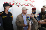 Iraqi Prime Minister Mustafa al-Kadhimi, center, speaks to the journalists as he stands with Lt. Gen. Abdul-Wahab al-Saadi, the counterterrorism forces commander, left, at thw Iraq-Iran border crossing of Mandali in northern province of Diyala, Iraq, Saturday, July, 11, 2020. Al-Kadhimi launched a campaign in the northern province of Diyala to enforce the proper payment of taxes on imported goods and recover
