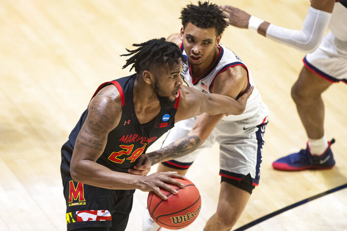 Maryland's Donta Scott (24) moves by Connecticut's James Bouknight during the first half of a first-round game in the NCAA men's college basketball tournament Saturday, March 20, 2021, at Mackey Arena in West Lafayette, Ind. (AP Photo/Robert Franklin)
