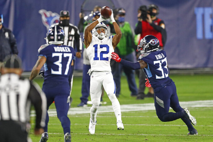 Indianapolis Colts wide receiver DeMichael Harris (12) catches a pass as he is defended by Tennessee Titans safety Amani Hooker (37) and cornerback Desmond King (33) in the first half of an NFL football game Thursday, Nov. 12, 2020, in Nashville, Tenn. (AP Photo/Wade Payne)