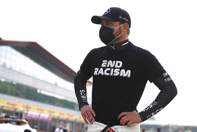 Mercedes driver Valtteri Bottas of Finland stands in the pit lane ahead of the 70th Anniversary Formula One Grand Prix at the Silverstone circuit, Silverstone, England, Sunday, Aug. 9, 2020. (Bryn Lennon, Pool via AP)