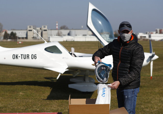 Dan Stastny, a pilot of a small sport plane, displays a snorkeling mask, modified to be a protection respirator for medical staff, that he will transport from a small Prague airport to a hospital in Ostrava some 400 kilometers (about 250 miles) east of Prague, Czech Republic, Sunday, April 5, 2020. Over 300 pilots in the Czech Republic have joined forces in a group of volunteers who use their private planes to distribute medical equipment all across the country. The