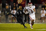 Oklahoma running back Seth McGowan (1) runs from Iowa State linebacker O'Rien Vance, left, during the first half an NCAA college football game, Saturday, Oct. 3, 2020, in Ames, Iowa. (AP Photo/Charlie Neibergall)