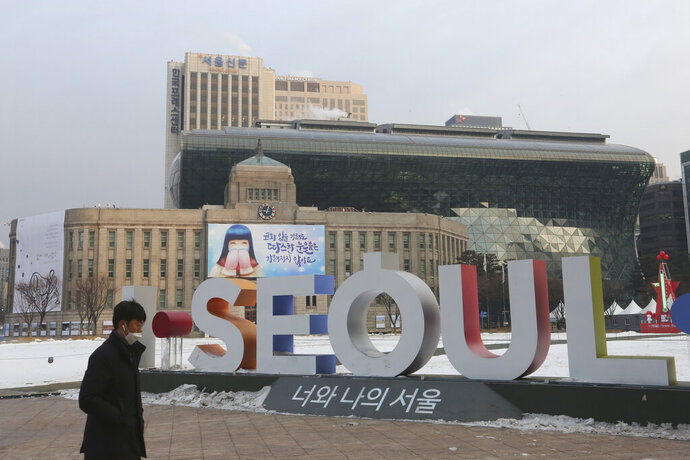 A man walks by the display of the capital city's logo near the Seoul City Hall in Seoul, South Korea, Tuesday, Jan. 12, 2021. The government of South Korea's capital is being criticized for a now-deleted online manual for pregnant women that contained sexist tips and gender stereotypes. (AP Photo/Ahn Young-joon)