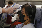 Stewardesses take temperatures of passengers as a preventive measure for the coronavirus on an Air China flight from Melbourne to Beijing before it land at Beijing Capital International Airport in China, Tuesday, Feb. 4, 2020. China said Tuesday the number of infections from a new virus surpassed 20,000 as medical workers and patients arrived at a new hospital and President Xi Jinping said