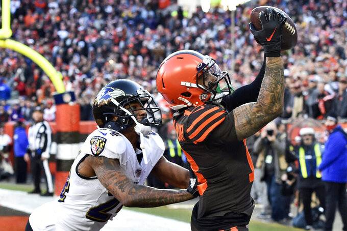 Cleveland Browns wide receiver Odell Beckham Jr., right, catches a 3-yard touchdown pass against Baltimore Ravens cornerback Marcus Peters during the second half of an NFL football game, Sunday, Dec. 22, 2019, in Cleveland. (AP Photo/David Richard)