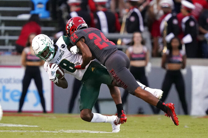 North Carolina State cornerback Derrek Pitts Jr. (24) tackles South Florida wide receiver Latrell Williams (8) during the first half of an NCAA college football game in Raleigh, N.C., Thursday, Sept. 2, 2021. (AP Photo/Gerry Broome)