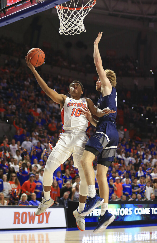 Florida guard Noah Locke (10) is fouled by North Florida forward Josh Endicott (21) during the first half of an NCAA college basketball game Tuesday, Nov. 5, 2019, in Gainesville, Fla. (AP Photo/Matt Stamey)