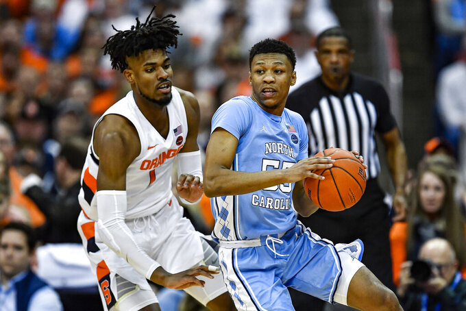 North Carolina guard Christian Keeling, right, is defended by Syracuse forward Quincy Guerrier during the second half of an NCAA college basketball game in Syracuse, N.Y., Saturday, Feb. 29, 2020. North Carolina defeated Syracuse 92-79. (AP Photo/Adrian Kraus)