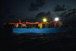 Dozens of migrants from different nationalities, mainly Somalia, Egypt and Morocco, including 14 minors and 4 women, wait to be assisted by a team of aid workers of the Spanish NGO Open Arms, after spending more than 20 hours at sea when fleeing Libya on board a precarious wooden boat, in international waters, in the Central Mediterranean sea, Tuesday, Sept. 8, 2020. (AP Photo/Santi Palacios)