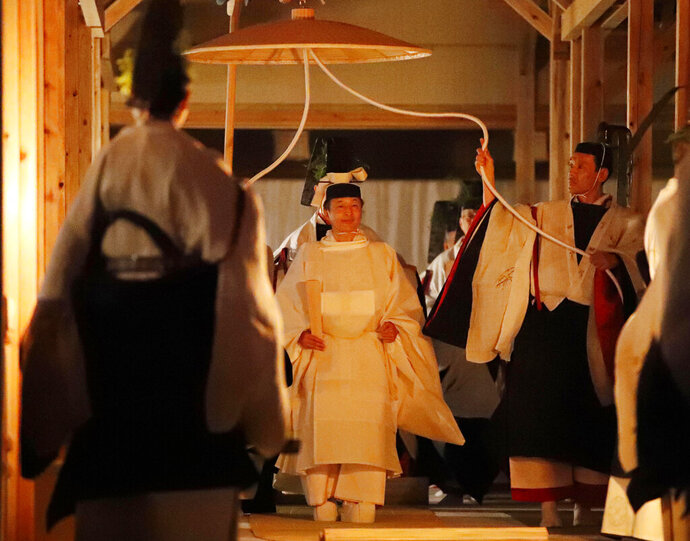 Japan's Emperor Naruhito, center, walks toward Yukiden, one of two main halls of the shrine for Daijosai, or great thanksgiving festival, at the Imperial Palace in Tokyo Thursday, Nov.  14, 2019. Naruhito performed a secretive and controversial ritual Thursday, a once-in-a-reign event to give thanks for good harvests, pray for the peace and safety of the nation and play host to his family's ancestral gods. (Kyodo News via AP)