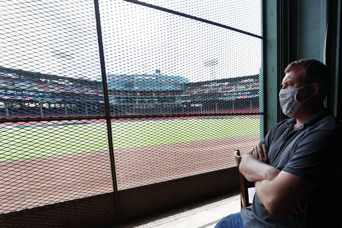 In this June 25, 2020, photo, Joe Hicks, Bleacher Bar director of operations, looks out at Fenway Park from the bar in Boston. Tucked under the center field seats at Fenway Park, down some stairs from Lansdowne Street in an area previously used as the visiting team's batting cage, is a sports bar that is preparing to reopen from the coronavirus shutdown. If Major League Baseball's plans remain on schedule, it may be one of the few places fans will be able to watch a game in person this season. (AP Photo/Elise Amendola)