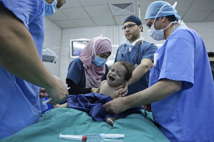 In this March 5, 2018 photo, one-year-old Syrian refugee Eman Zatima is prepared by medical staff for surgery, at a hospital in Amman, Jordan. Eman, who has a heart defect, received a life-saving pro bono surgery from doctors sent by the Vatican's Bambino Gesu Hospital. The infant is one of the few lucky Syrian refugees with severe medical conditions to get the needed treatment. Dozens more are left untreated each month because of funding constraints in overwhelmed refugee host countries in the region. (AP Photo/Raad Adayleh)