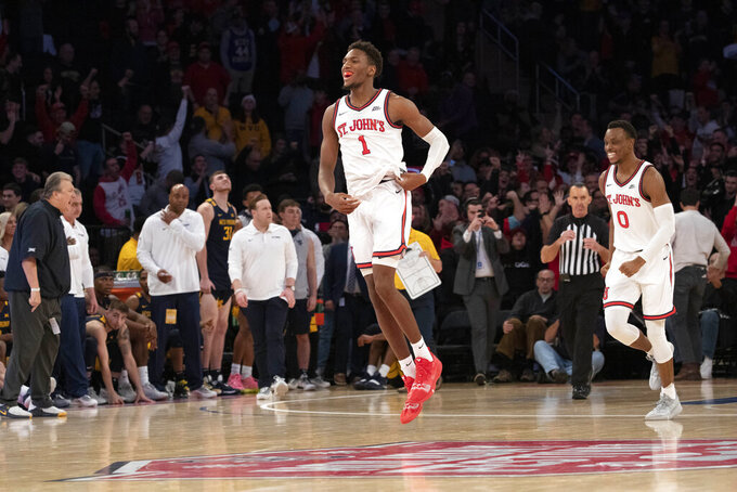 St. John's Josh Roberts (1) and Mustapha Heron (0) react at the final buzzer as they defeat West Virginia 70-68 in an NCAA college basketball game, Saturday, Dec. 7, 2019, in New York. (AP Photo/Mark Lennihan)