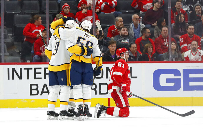 Nashville Predators center Matt Duchene (obscured) celebrates his goal with Filip Forsberg (9) and Roman Josi (59) as Detroit Red Wings center Frans Nielsen (81) kneels on the ice in the second period of an NHL hockey game Monday, Nov. 4, 2019, in Detroit. (AP Photo/Paul Sancya)