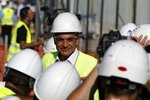 Greece's Prime Minister Kyriakos Mitsotakis wearing a helmet and plastic glasses stands at the old airport in Athens, Friday, July 3, 2020. Mitsotakis inaugurated the start of construction work on a long-delayed major development project at the prime seaside site of the old Athens airport. The development of the 620-hectare (1,500-acre) Hellenikon site was a key element of the privatization drive that was part of Greece's international bailouts. (AP Photo/Thanassis Stavrakis)