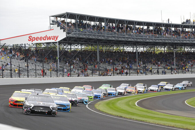 FILE - In this Sept. 8, 2019, file photo, Kevin Harvick leads the field through the first turn on the start of the NASCAR Brickyard 400 auto race at Indianapolis Motor Speedway in Indianapolis. The once frosty schism between the two biggest racing series in the United States has thawed and NASCAR's elite Cup Series will share a venue with IndyCar on the same weekend for the first time in history. (AP Photo/Darron Cummings, File)