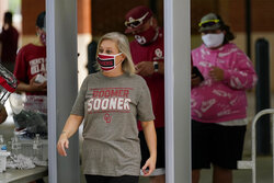 Fans in masks walk through metal detectors as they arrive for the Missouri State vs. Oklahoma NCAA college football game Saturday, Sept. 12, 2020, in Norman, Okla. (AP Photo/Sue Ogrocki, Pool)