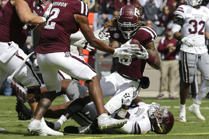 Texas A&M wide receiver Kendrick Rogers (13) rolls over Mississippi State defensive tackle Jaden Crumedy (84) for a touchdown after a catch and run during the first half of an NCAA college football game, Saturday, Oct. 26, 2019, in College Station, Texas. (AP Photo/Sam Craft)