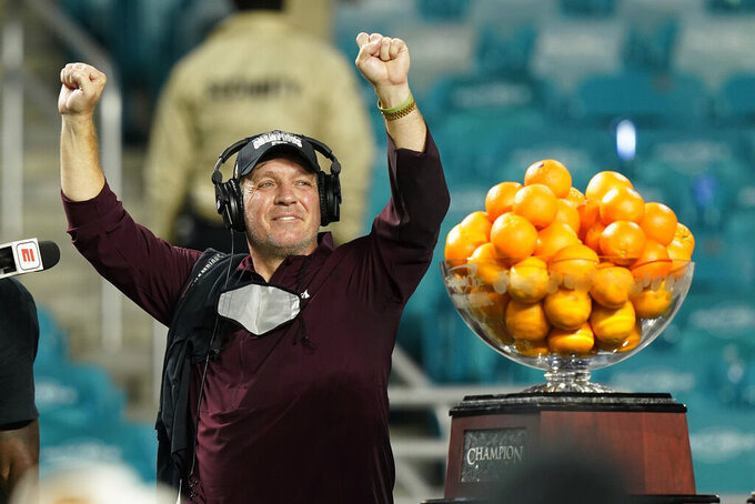 Texas A&M head coach Jumbo Fisher raises his hands during the trophy presentation at the Orange Bowl NCAA college football game, Saturday, Jan. 2, 2021, in Miami Gardens, Fla. Texas A&M defeated North Carolina 41-27. (AP Photo/Marta Lavandier)