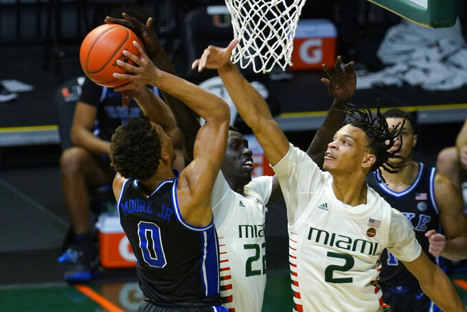 Miami guard Isaiah Wong (2) and forward Deng Gak (22) attempt to stop a drive to the basket by Duke forward Wendell Moore Jr. (0) during the second half of an NCAA college basketball game, Monday, Feb. 1, 2021, in Coral Gables, Fla. Miami defeated Duke 77-75. (AP Photo/Marta Lavandier)