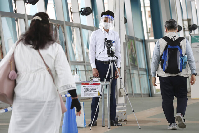 Visitors walk past a thermography camera monitors as the Hakkeijima Sea Paradise amusement park opens after a two-month closure due to the preventative measures to help curb the spread of the coronavirus in Yokohama near Tokyo, Monday, June 1, 2020. (AP Photo/Koji Sasahara)