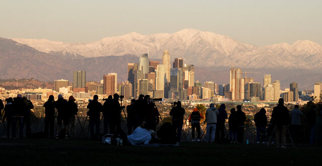 Photographers set their equipment as they are waiting to photograph the moon rising over snow covered mountains, behind the downtown Los Angeles skyline at Kenneth Hahn State Recreation Area Tuesday, Dec. 29, 2020, in Los Angeles. (AP Photo/Ringo H.W. Chiu)