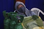 A woman sleeps next to her empty oxygen cylinder to refill as she waits for the shop to open in the San Juan neighborhood of Lima, Peru, Monday, Aug. 3, 2020. Peruvian authorities calculate that more than a quarter of Lima's population may have been infected with the new coronavirus, and Peru has the highest death rate per million in the Americas. (AP Photo/Martin Mejia)