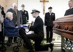 Rita Mendonsa, left, receives the flag that draped her husband George's casket during funeral services at St. Columba Cemetery in Middletown, R.I., Friday, Feb. 22, 2019. George Mendonsa, the sailor sailor photographed kissing a woman in Times Square in New York at the end of World War, died Sunday at age 95. (AP Photo/Michael Dwyer)