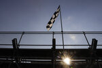 A checkered flag blows in the breeze as the sun begins to set during a NASCAR Cup Series auto race at Indianapolis Motor Speedway in Indianapolis, Sunday, July 5, 2020. (AP Photo/Darron Cummings)