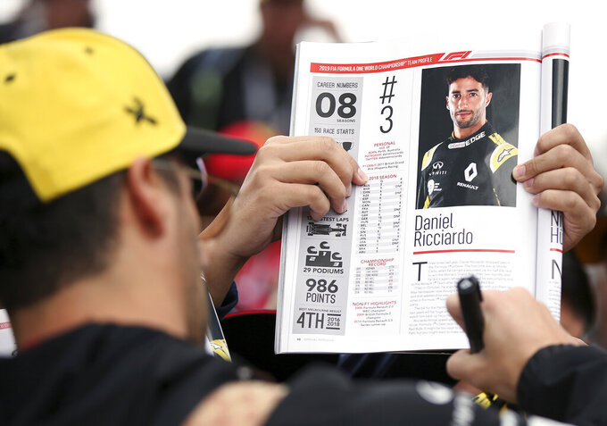 Renault driver Daniel Ricciardo of Australia signs autographs as he arrives at the track of the Australian Grand Prix in Melbourne, Australia, Friday, March 15, 2019. The first race of the year is Sunday. (AP Photo/Rick Rycroft)