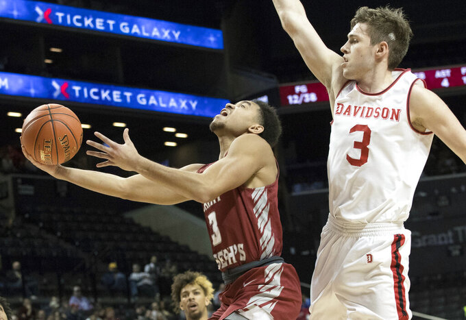 Saint Joseph's guard Jared Bynum, left, goes to the basket past Davidson guard Jon Axel Gudmundsson (3) during the second half of an NCAA college basketball game in the Atlantic 10 Conference tournament, Friday, March 15, 2019, in New York. Davidson won 70-60. (AP Photo/Mary Altaffer)