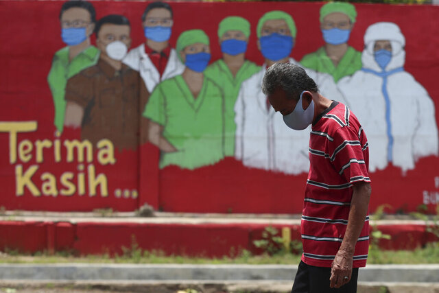 A man wearing a face mask walks past a coronavirus-themed mural in Jakarta, Indonesia, Thursday, Oct. 1, 2020. (AP Photo/Achmad Ibrahim)