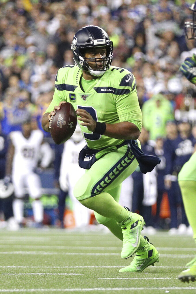 Seattle Seahawks quarterback Russell Wilson (3) looks downfield for a receiver in an NFL game against the Los Angeles Rams, Thursday, Oct. 3, 2019, in Seattle. The Seahawks defeated the Rams 30-29. (Margaret Bowles via AP)