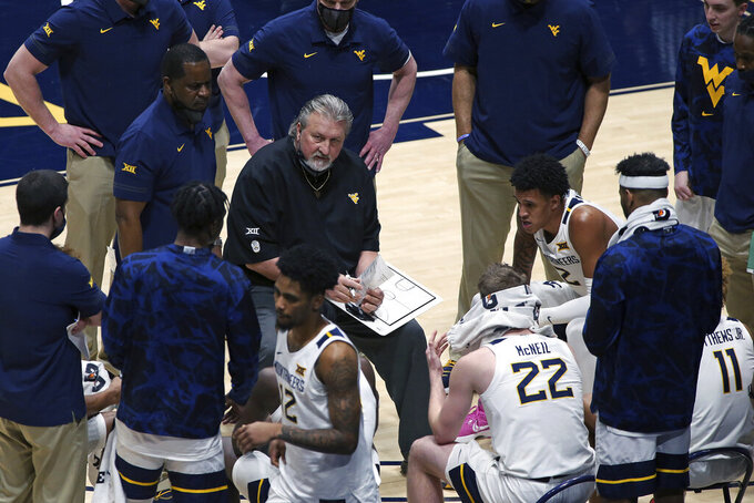 West Virginia coach Bob Huggins speaks with players during the second half of an NCAA college basketball game against Texas Christian Thursday, March 4, 2021, in Morgantown, W.Va. (AP Photo/Kathleen Batten)