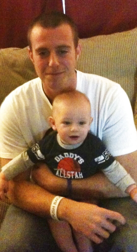 This 2012 photo provided by courtesy of the Ellis family shows Terral Ellis Jr. and his child. A federal negligence and wrongful death lawsuit against a northeastern Oklahoma county, its sheriff, former sheriff, jailers, nurse and others alleges Ellis, an inmate, was allowed to die despite repeated pleas for help that were captured on jail videotape. (Courtesy of the Ellis family via AP)