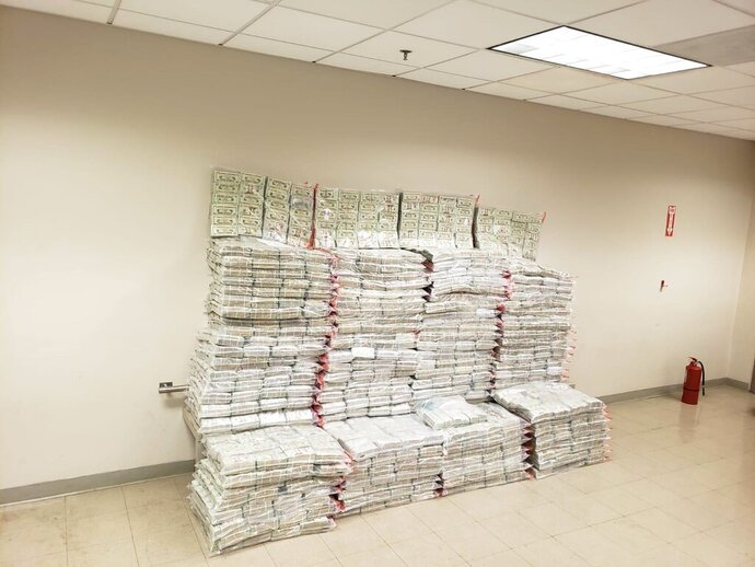 This photo provided by the Drug Enforcement Administration Caribbean Division Office shows what it reports is 27 million dollars seized on Aug. 29 as part of the Inter-agency operation, at the US Customs and Border Protection, CBP, headquarters in San Juan, Puerto Rico, Monday, Aug. 31, 2020. CBP says the undeclared currency was found inside boxes bound to St. Thomas, US Virgin Islands.  (Drug Enforcement Administration Caribbean Division Office via AP)